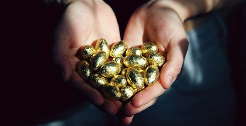 hands holding a pile of gold eggs